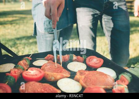 Freunde Grill und dem Mittagessen in der Natur. Paar Spaß beim Essen und Trinken zu einem Pic-nic - glückliche Leute an der Grillparty - Stockfoto