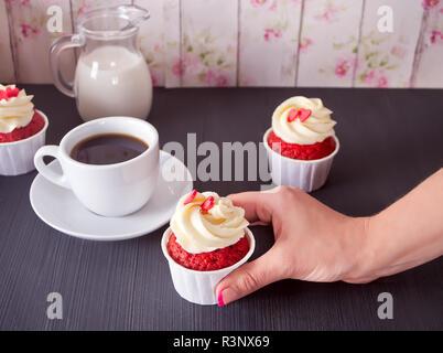 Tasse Kaffee und drei Cupcakes mit Herzen auf dem Holztisch. Frau mit Cupcake. - Stockfoto