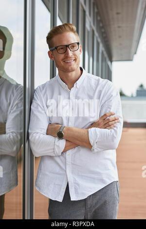 Portrait von lächelnden Geschäftsmann lehnte sich gegen Fenster