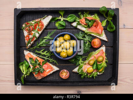 Sandwiches mit gesalzener Fisch rot, Cherry Tomaten, Rucola, Quark und Kräuter in einem schwarzen Holz- fach, Ansicht von oben - Stockfoto