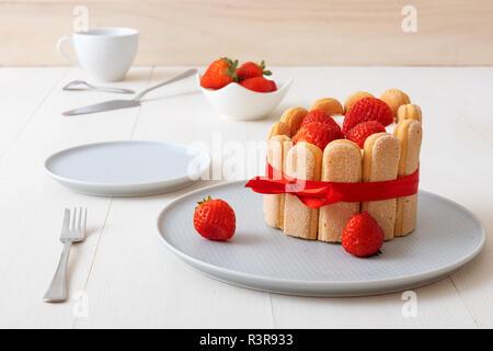 Charlotte, französische Dessert mit Erdbeeren, gefesselt mit einem roten Band, Tasse, Schüssel mit Erdbeeren auf weißer Tisch. - Stockfoto