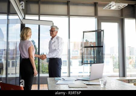 Geschäftsmann und Frau Händeschütteln im Büro