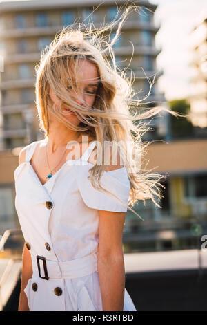 Blonde junge Frau mit windswept Haar zu tragen weißes Kleid im Freien - Stockfoto