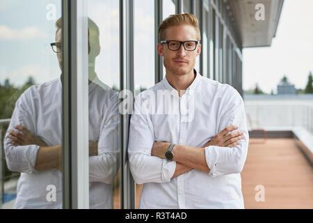 Portrait von zuversichtlich Geschäftsmann lehnte sich gegen Fenster