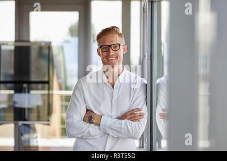 Portrait von lächelnden Geschäftsmann im Amt lehnte sich gegen Fenster