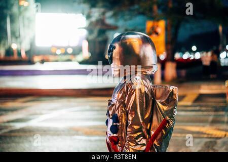Spaceman auf einer Straße in der Stadt bei Nacht von strahlenden Projektionsfläche angezogen