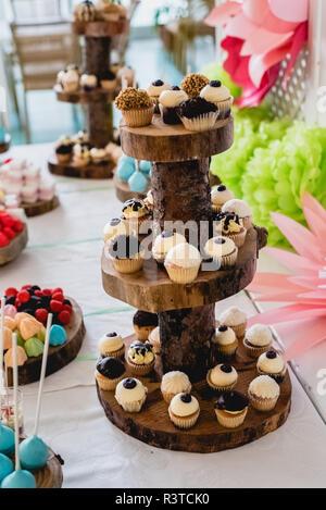 Desserts und Hochzeitstorte mit sehr süßen Cupcakes auf einer Veranstaltung. - Stockfoto