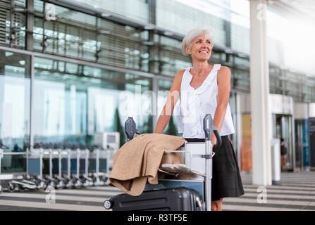 Lächelnd senior Frau drücken Gepäckwagen am Flughafen Stockfoto