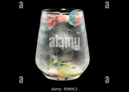 Gin und Tonic mit Jelly Beans mit isolierten schwarzen Hintergrund - Stockfoto