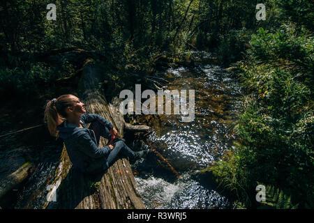 Schöne Mädchen sitzt auf Anmelden und Chillen nach Reisen. Frau Reisende im Sommer geht auf hölzernen Brücke im Hintergrund von Wald. Bridged liegt auf der Ri - Stockfoto