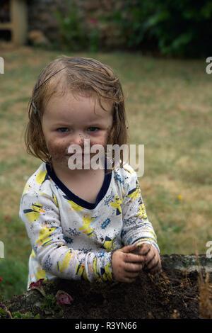 Kleinkind spielen in den Schmutz im Garten - Stockfoto