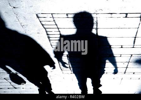 Unscharfe Silhouette und Schatten von zwei Menschen zu Fuß die Stadt Straße in der Nacht - Stockfoto