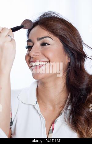 Lächelnde Frau mit einem Make-up-Pinsel in der Nähe von ihr Gesicht - Stockfoto