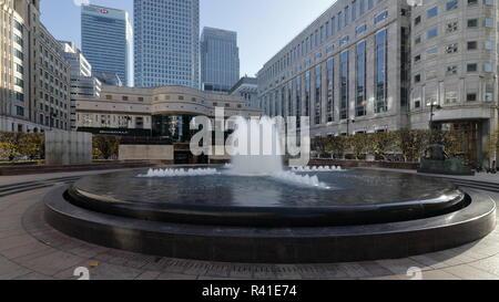 Cabot Square Brunnen in Canary Wharf London. Am frühen Sonntagmorgen. Letzten warmen Tage im Herbst 2018. In wenigen Minuten werden die Menschen beginnen, gehen Sie einkaufen - Stockfoto