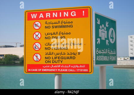 Zweisprachige Warnzeichen, kein Schwimmen, kein Tauchen, kein Angeln, keine Rettungsschwimmer, Sammelplatz, Arabisch und Englisch, Bahrain, Manama, Bahrain Stockfoto