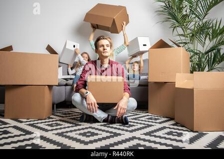 Foto von ernster Mann sitzen auf dem Boden und Frauen mit Jungen und Mädchen sitzen auf graue Sofa unter Kartons - Stockfoto