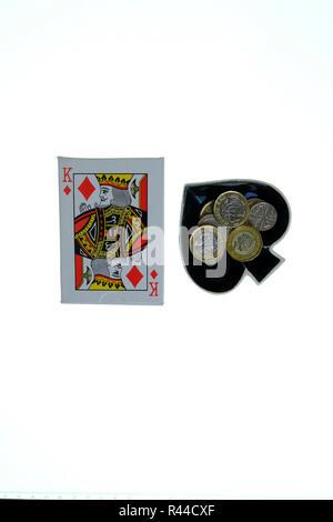 Packung mit traditionellen Spielkarten auf weißem Hintergrund mit Ace of Spades geformte Schmuckstück Schüssel auf die Seite mit Loose Change. - Stockfoto