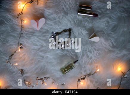 Flatlay aus einem offenen Buch, zwei Papier origami in Herzform, Rot lisptick und Weihnachtsbeleuchtung - Stockfoto