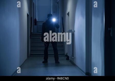 Einbrecher mit Taschenlampe und Brecheisen im Büro Flur - Stockfoto