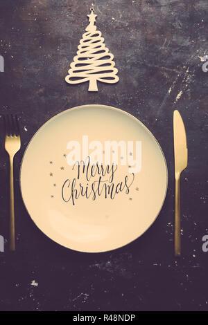 """Weihnachten Luxus Urlaub Konzept, mit einer Platte mit Text beeindruckt """"Frohe Weihnachten"""" Weihnachten Kugeln und gold Dekoration über einen grünen metallischen Hintergrund - Stockfoto"""