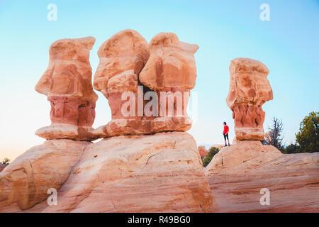 Schöne Sicht der männlichen Wanderer stehen zwischen erstaunliche Vier Hoodoos Sandstein Felsformationen in Devil's Garten im schönen Abendlicht bei Sonnenuntergang, Grand - Stockfoto