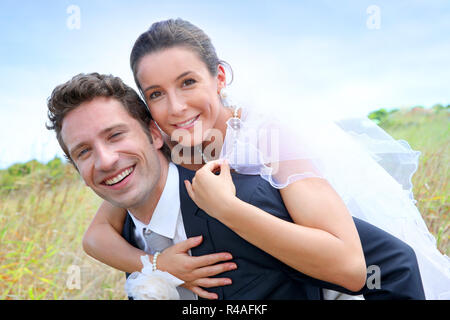 Bräutigam und Braut pigguback Fahrt zu - Stockfoto