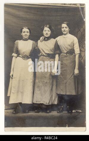 WW1 Ära Portrait von 3 Mädchen, vielleicht Lancashire Cotton Mill Arbeitskräfte, Clogs und Schürzen mit Haken - wie Werkzeug- und Schere in Ihre speziell für Gürtel, ca. 1915,1918, Großbritannien - Stockfoto