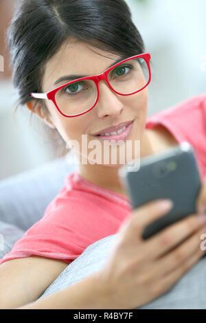Brunette Mädchen mit roten Brille lesen Nachricht auf dem Smartphone - Stockfoto