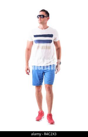 Ernst Macho im Sommer T-Shirt und Shorts mit Sonnenbrille nähert und sich mit Haltung. Voller Körper auf weißem Hintergrund. - Stockfoto