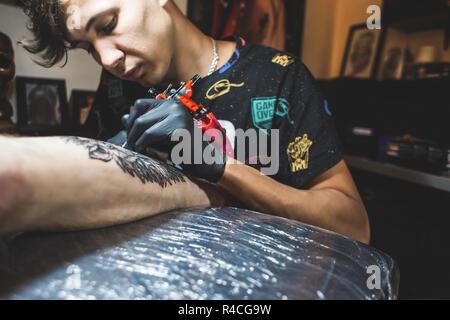 Die tattoo Artist erstellt ein Bild auf dem Körper eines Mannes. close-up Der tätowiermaschinen und Hände - Stockfoto