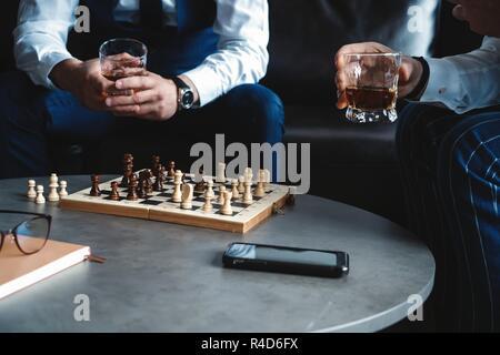 Sie bewegen! Zwei junge schöne Männer in Anzügen Schach spielen und lächelnd beim Sitzen im Innenbereich - Stockfoto