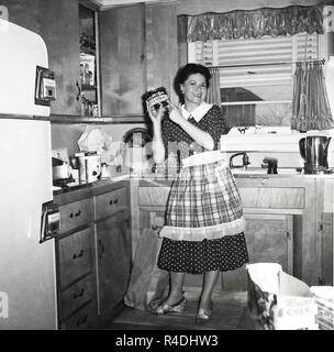 1950er Jahren Frau Hausfrau In Küche Auf Besen Gelehnt Stand