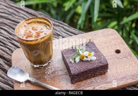 Latte Kaffee und Chocolate Brownie Kuchen auf Schneidebrett auf Holz Tabelle auf Baum Hintergrund. Latte Kaffeepause Zeit für Essen und Trinken Kategorie Stockfoto