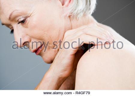 Eine ältere Frau mit der Hand auf die Schulter - Stockfoto