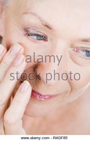 Eine ältere Frau Augencreme anwenden - Stockfoto