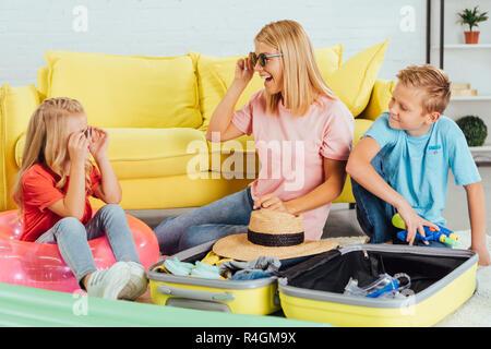 Freundliche Familie Verpackung Gepäck für für Sommer Urlaub, Spaß zu haben und zu versuchen, auf Gläsern, Travel Concept - Stockfoto