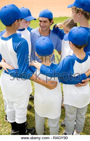 Little League Baseball-Teams im Huddle mit ihrem Trainer - Stockfoto