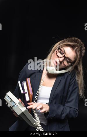 Überarbeitete junge geschäftsfrau mit Notebooks im Gespräch per Telefon isoliert auf Schwarz - Stockfoto