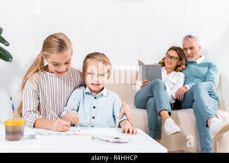 Schwester und Bruder Malerei am Tisch, während ihre Großeltern auf dem Sofa hinter zu Hause sitzen - Stockfoto