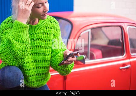 Mode farbige Konzept Bild mit blonden kaukasische Mädchen stehen in der Nähe von einem roten Vintage altes Auto mit Blue Steel Wand im Hintergrund. Urban und Farben wit - Stockfoto