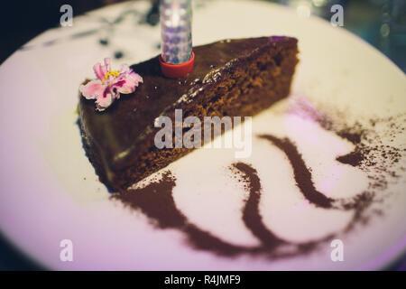 Köstliche Schokolade Kuchen auf dem Teller auf dunklem Hintergrund. - Stockfoto