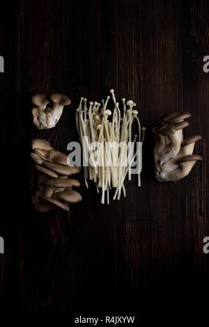 Verschiedene rohe Pilze auf alten Holztisch. Enoki, Shiitake und Austernpilze - Stockfoto