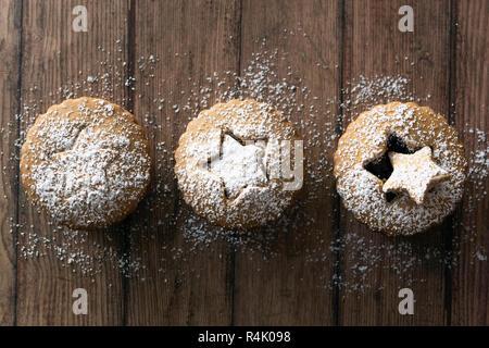 Drei Lebkuchen Obstkuchen mince bestäubt mit Puderzucker auf einer hölzernen Hintergrund. - Stockfoto