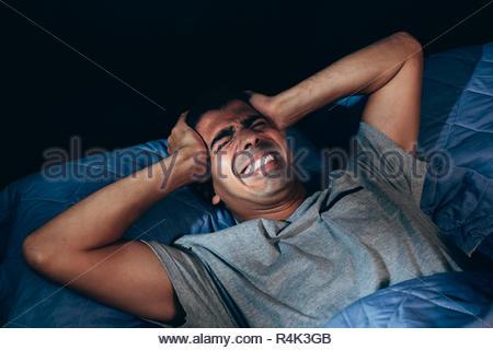 Hübscher junger Mann leidet unter Kopfschmerzen, während nachts im Bett liegend - Stockfoto