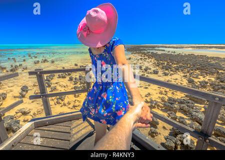 Frau in hat die Hand ihrer Freundin auf Holz weg an die Stromatolithen Hamelin Pool. Marine Reserve in Shark Bay, Western Australia. Ein Mädchen genießt der Australischen Reiseziel. Mir POV Folgen. - Stockfoto