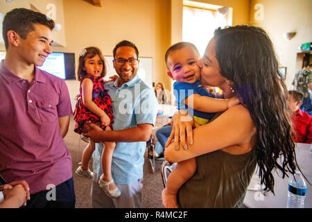 Ein Hispanic paar Hug Ihre jungen Kinder während der Wartezeit für eine Klasse, die auf die Werte der Familie zu einem Laguna Niguel, CA, Katholische Kirche. - Stockfoto
