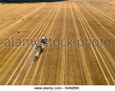 Antenne Overhead von Traktor Ballenpresse Strohballen in Feld nach der Weizenernte im Sommer auf der Farm - Stockfoto