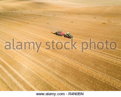 Antenne des Traktors und der Ballenpresse Strohballen in Feld nach der Weizenernte im Sommer auf der Farm - Stockfoto