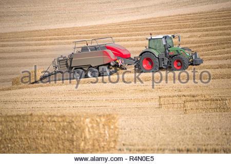 Traktor und Ballenpresse Strohballen in Feld nach dem Sommer Weizenernte auf der Farm - Stockfoto