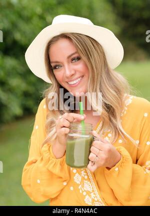 Lächelnde junge Frau mit Smoothie in Mason jar - Stockfoto